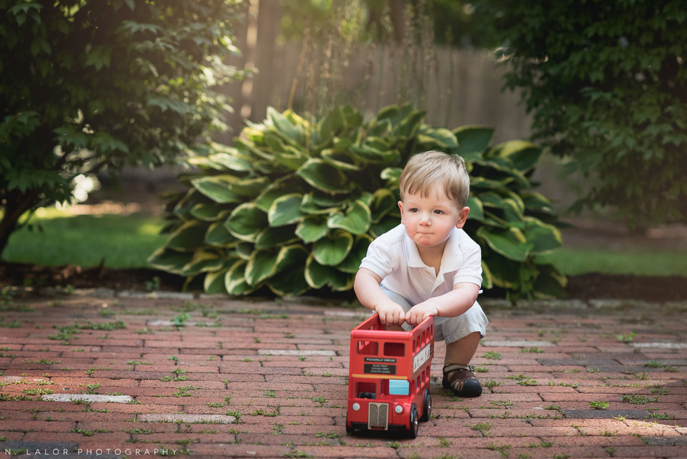Toddler playing with a London bus toy in the back yard. Naturally styled portrait by N. Lalor Photography.