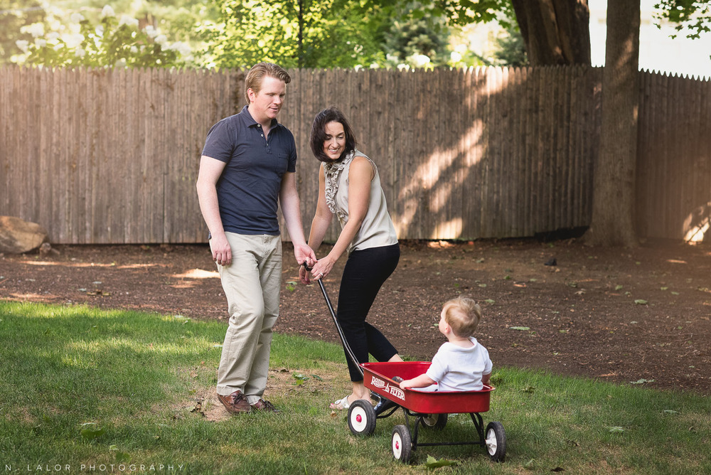 Parents pulling their son as he rides a Radio Flyer wagon. Naturally styled family photo by N. Lalor Photography.