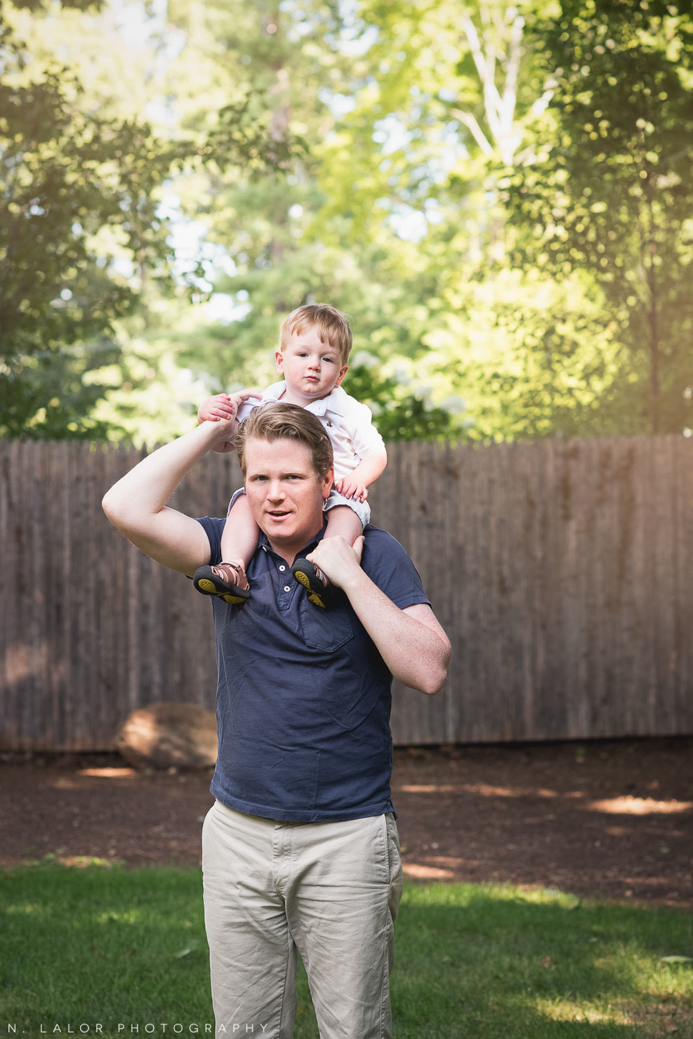 Toddler riding his dad's shoulders in the back yard. Naturally styled family photo by N. Lalor Photography.