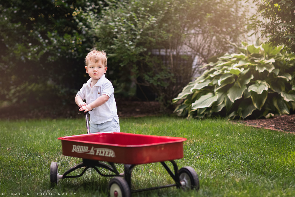 Toddler with his red Radio Flyer wagon. Naturally styled lifestyle portrait by N. Lalor Photography.