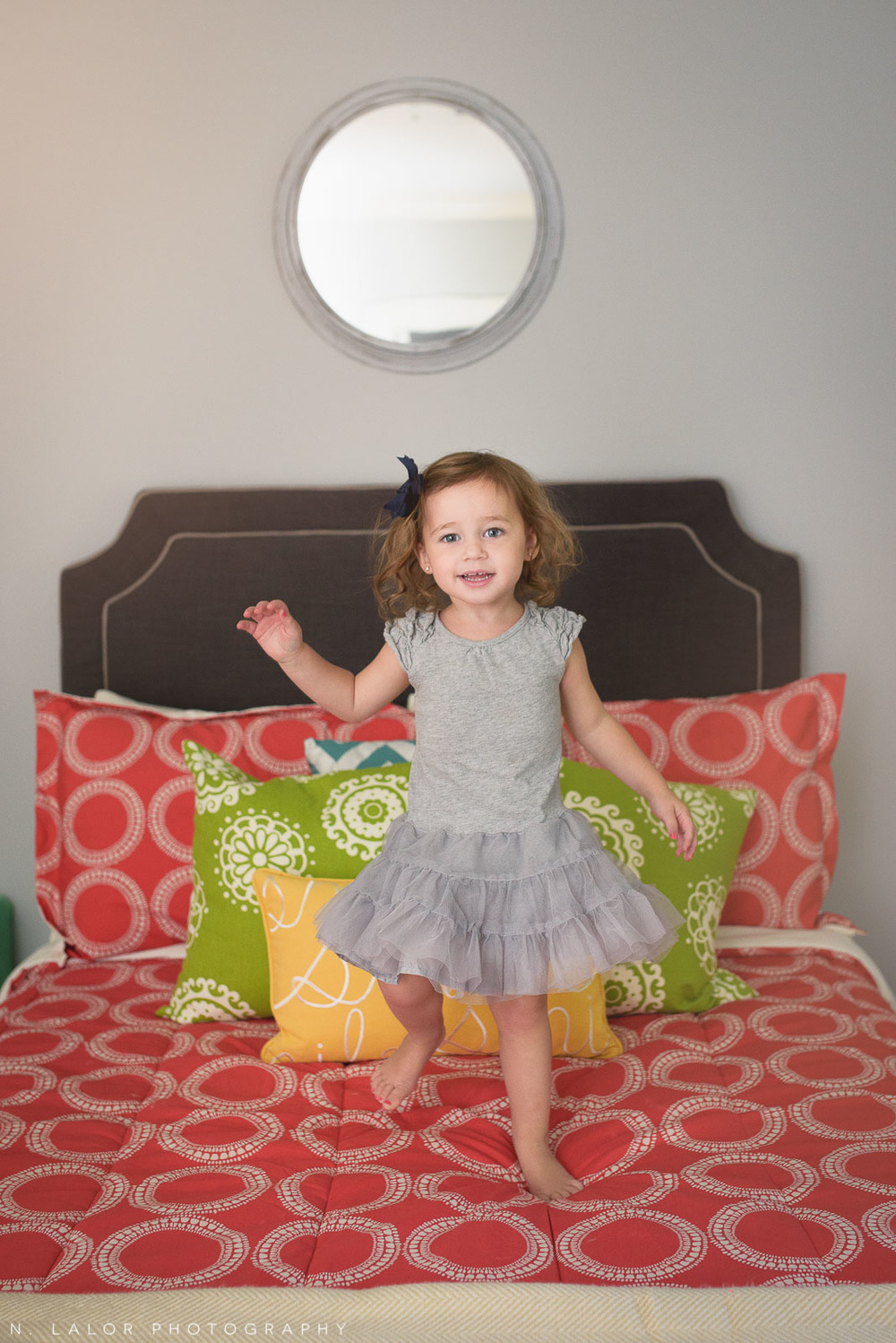 2-year old girl jumping on the bed in her room. Lifestyle portrait by N. Lalor Photography.