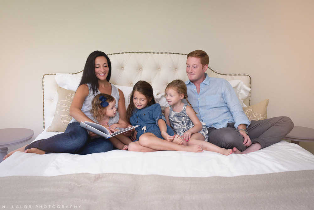 Naturally styled family portrait - reading a story on the bed. Photograph by N. Lalor Photography.