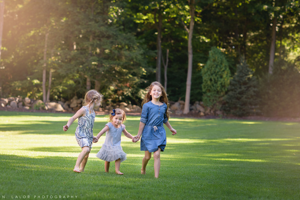Three sisters walking and holding hands in the back yard. Naturally styled photo by N. Lalor Photography.
