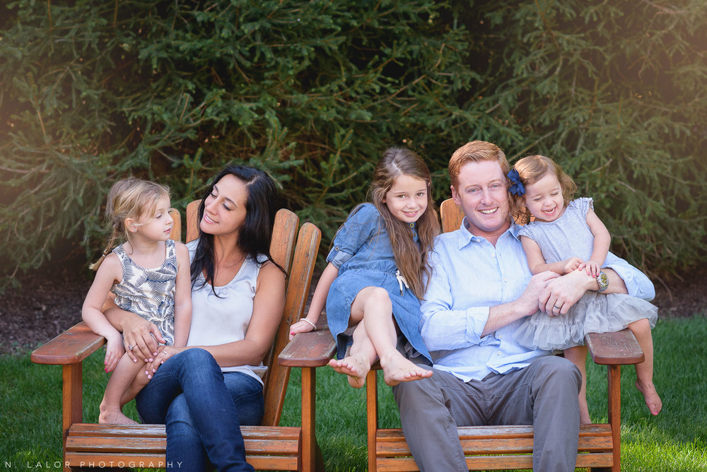 Lifestyle portrait of a family of five, sitting on adirondack chairs in their back yard. Lifestyle portrait by N. Lalor Photography.