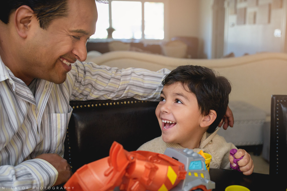 Happy smiling 4-year old playing play-doh with dad. Lifestyle portrait by N. Lalor Photography.