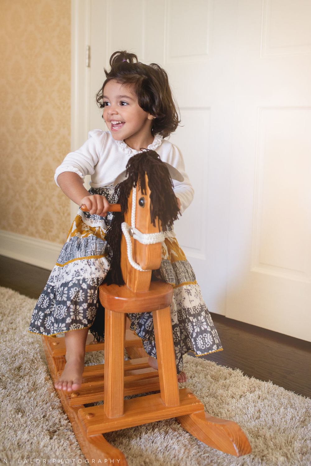 Having fun on a rocking horse. 2-year old girl portrait by N. Lalor Photography.