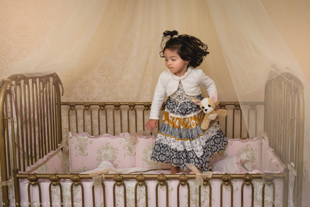 Toddler girl jumping on bed. Lifestyle portrait by N. Lalor Photography.