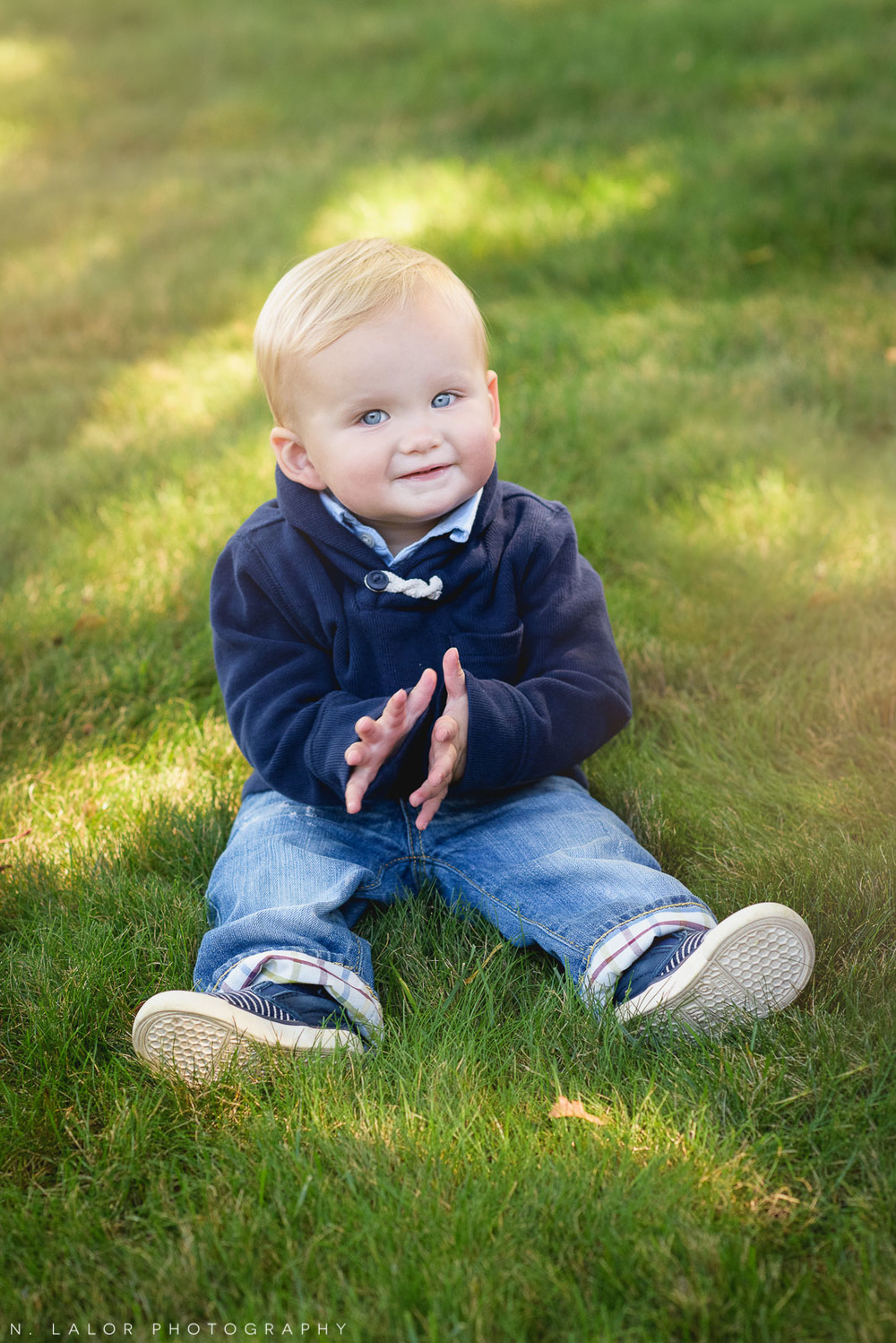 Adorable 1-year old boy sitting on grass. Lifestyle portrait by N. Lalor Photography. Fairfield, CT.