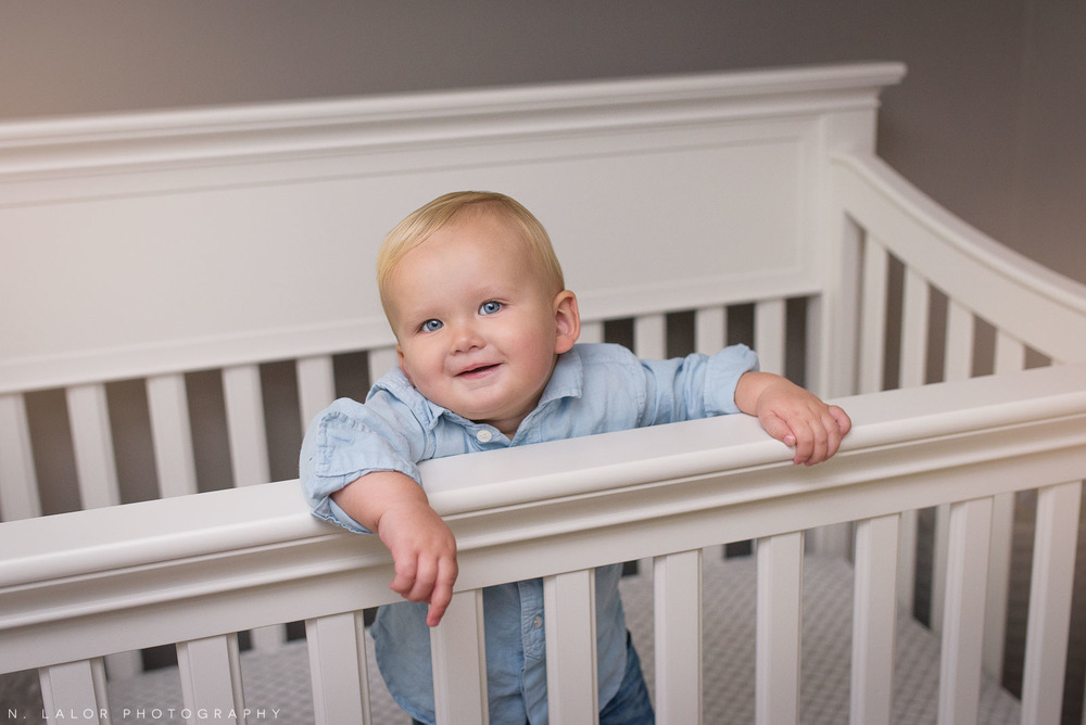 1-year old boy smiling while standing in his crib. Lifestyle portrait by N. Lalor Photography.