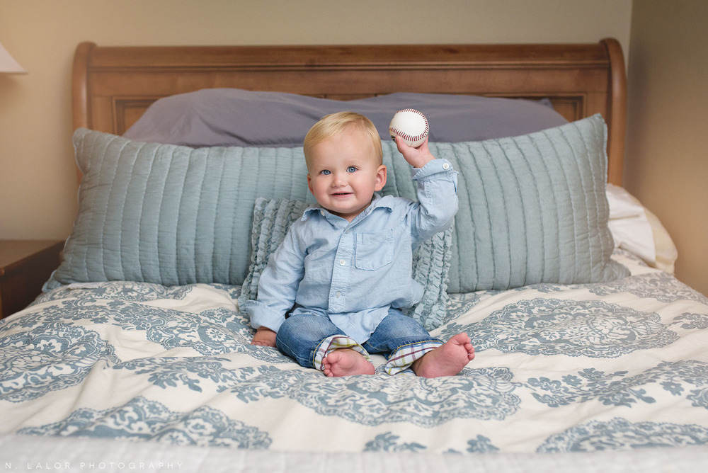 1-year old boy with baseball. In-home lifestyle portrait by N. Lalor Photography. Fairfield Connecticut.
