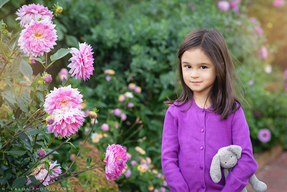 Outdoor portrait of a 5-year old girl next to pink flowers. Waveny Park New Canaan. Photo by N. Lalor Photography.