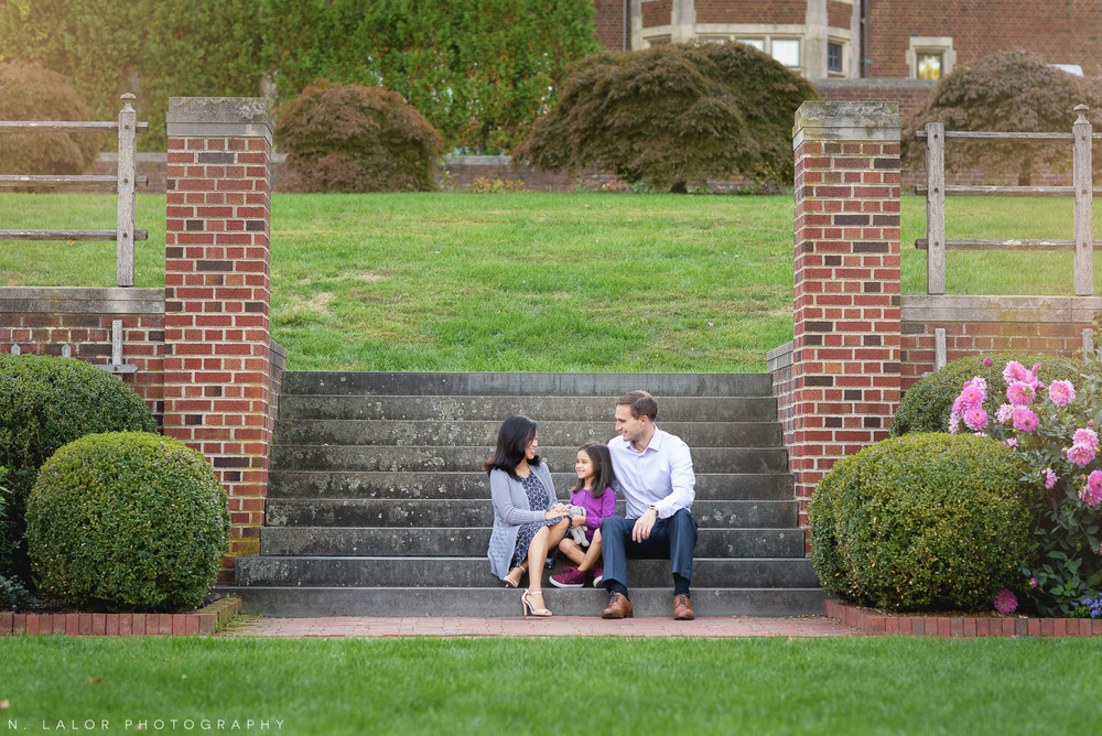 Family on steps in the garden by Waveny House. Lifestyle portrait by N. Lalor Photography. Waveny Park, New Canaan, Connecticut.