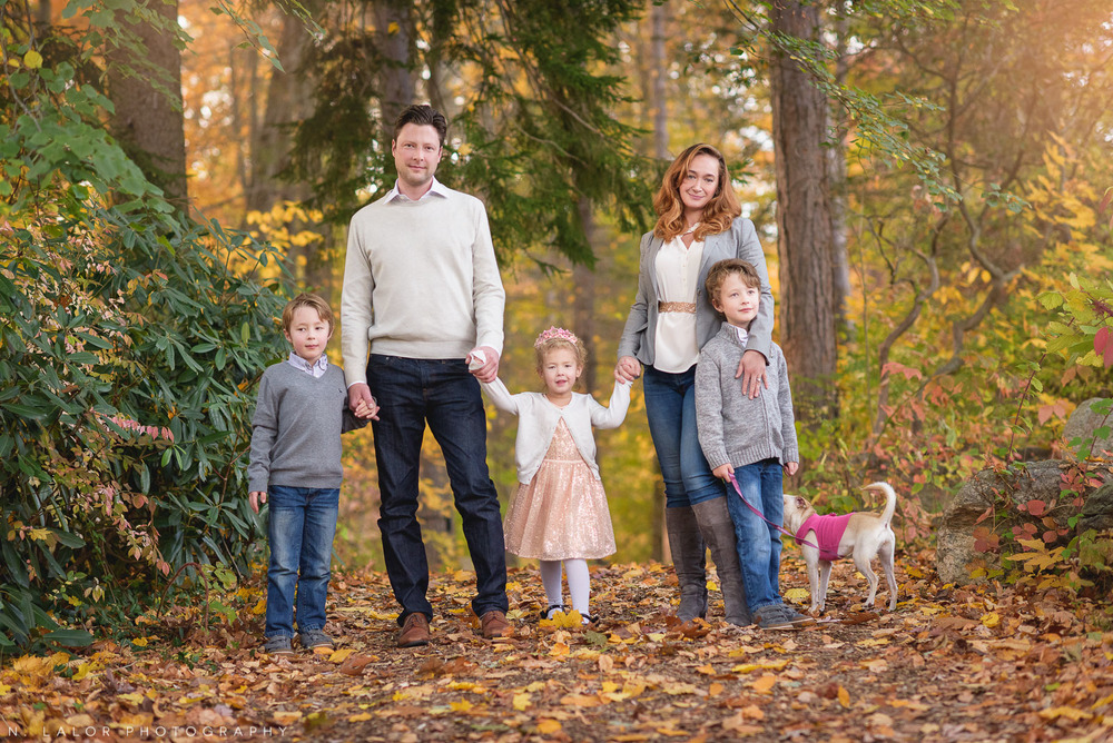 Lifestyle family photo in the woods with Fall leaves. Portrait by N. Lalor Photography. New Canaan Nature Center.