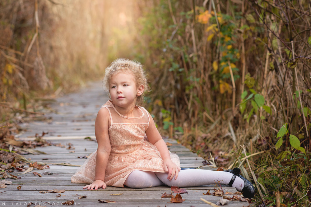 4-year old girl sitting on a boardwalk at the New Canaan Nature Center. Portrait by N. Lalor Photography.