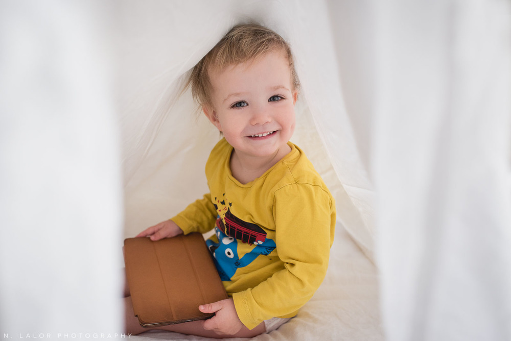 Smiling two year old toddler under the sheets. Photo by N. Lalor Photography.