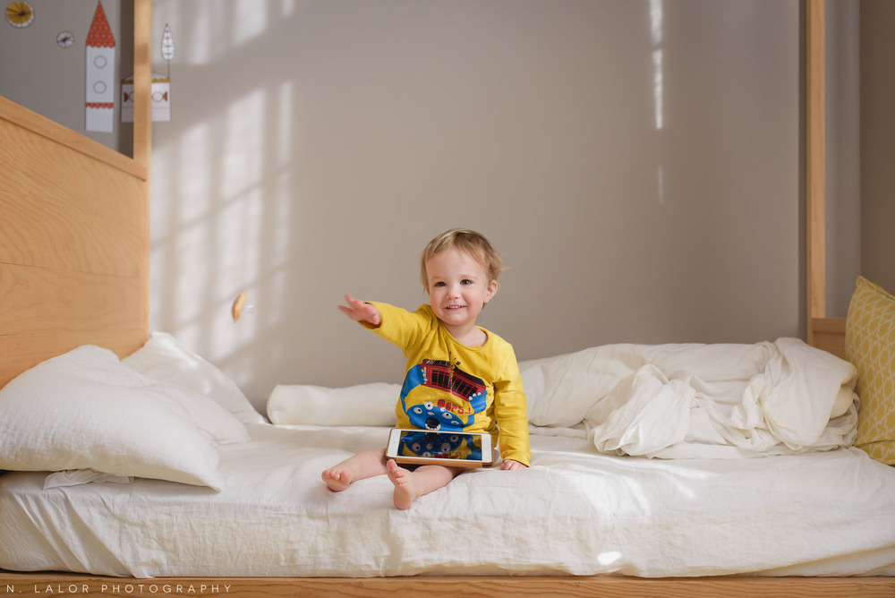 Two year old boy throwing a little heart while sitting on his floor bed. Photo by N. Lalor Photography.