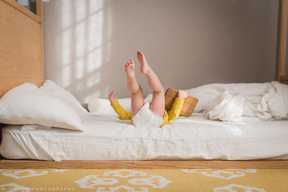 Two year old boy toddler falling over on his floor bed, while holding his iPad. Photo by N. Lalor Photography.