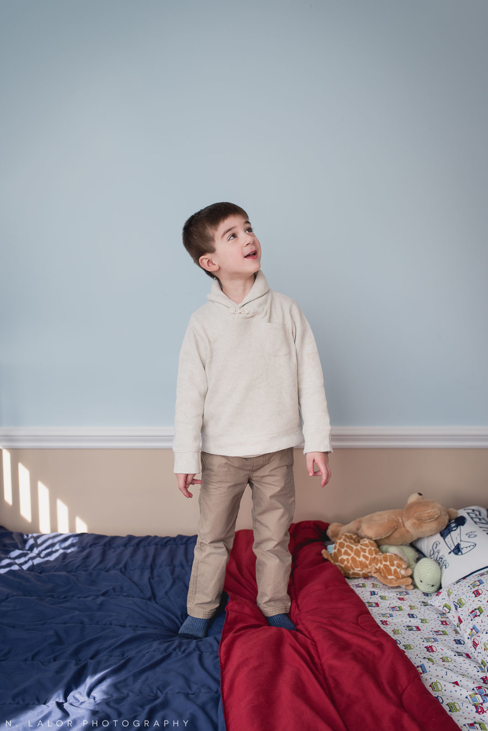 4-year old boy standing on his beds in his room. Lifestyle photo by N. Lalor Photography.