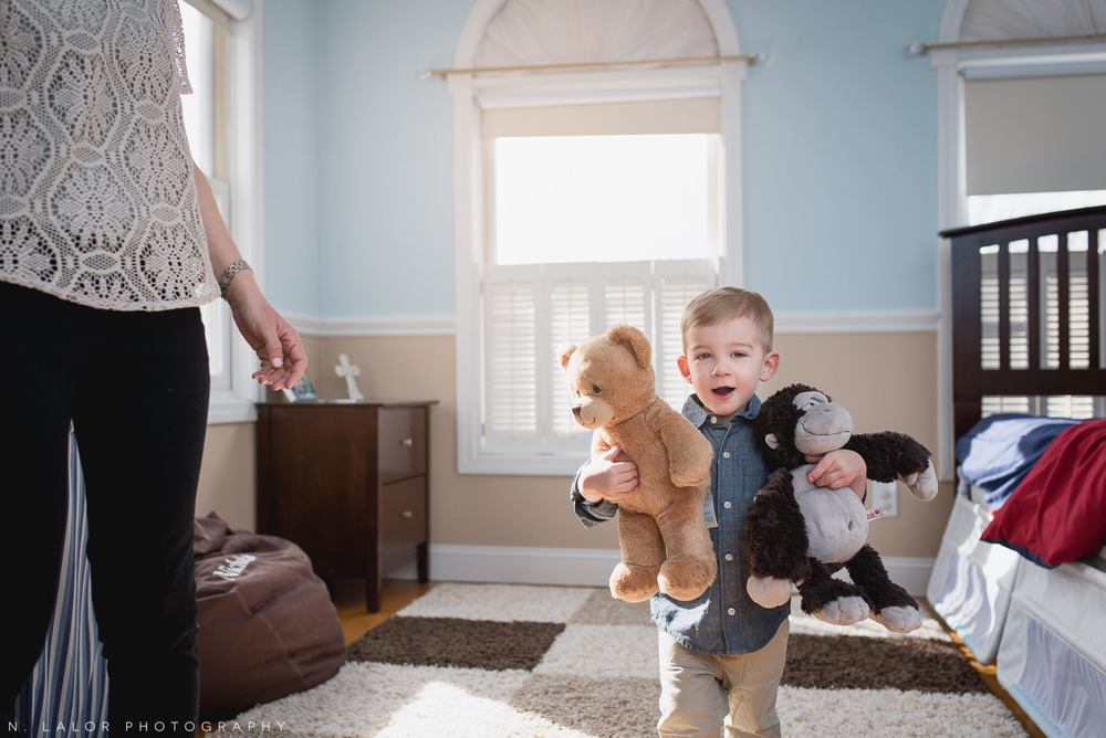 Little toddler boy stealing stuffed animals from his brother's room. Editorial family session by N. Lalor Photography.