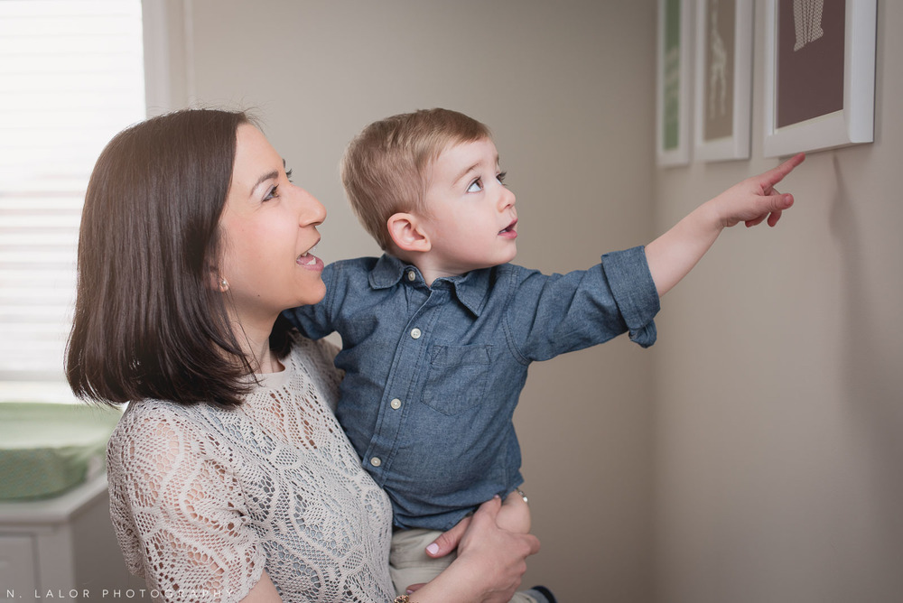 Toddler son looking at framed pictures on his wall with Mom. Family photo session by N. Lalor Photography. Fairfield County, CT.