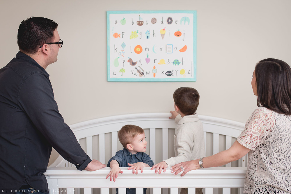 Family of four looking at the alphabet print in the room. Lifestyle photo session with N. Lalor Photography.