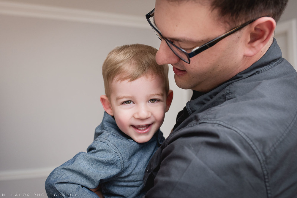Toddler boy snuggles with Dad. Casual and fun family photoshoot by N. Lalor Photography.