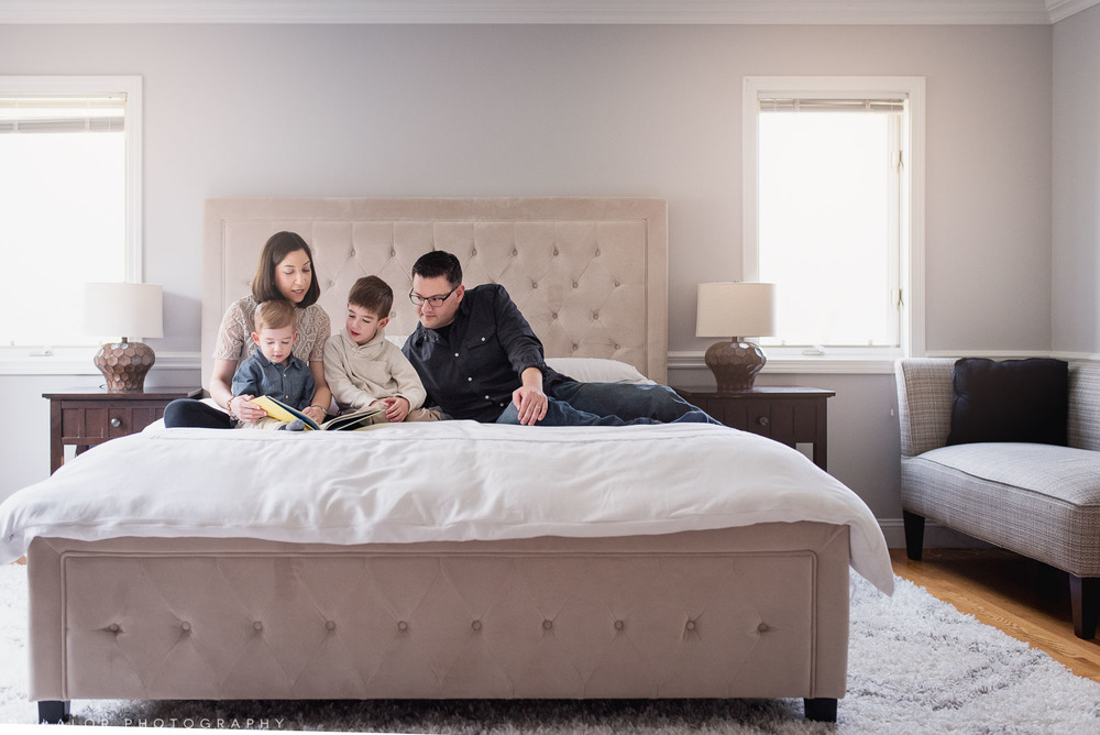 Family reading time in the big bed. Lifestyle photo by N. Lalor Photography. Fairfield County, CT.