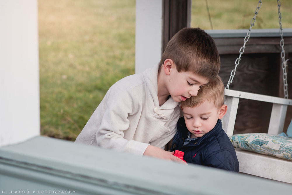 Two brothers, helping each other. Lifestyle photo by N. Lalor Photography. Fairfield County, CT.