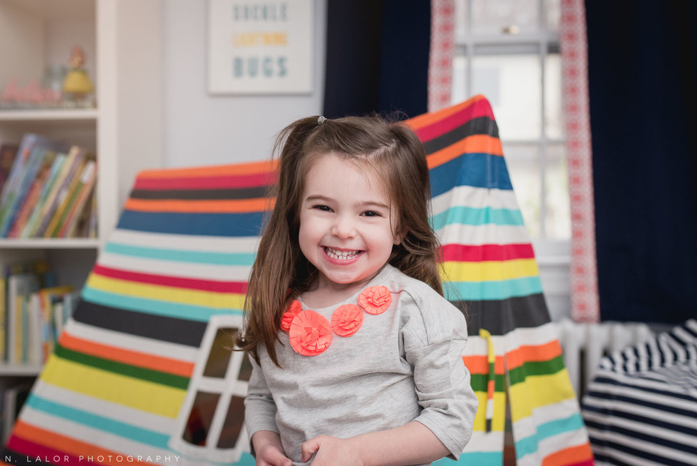 Happy 3-year old girl in her room. Lifestyle portrait by N. Lalor Photography.