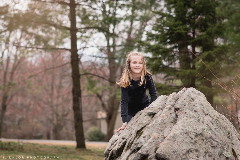 7-year old girl fearlessly climbing a huge boulder in her back yard. Photo by N. Lalor Photography.
