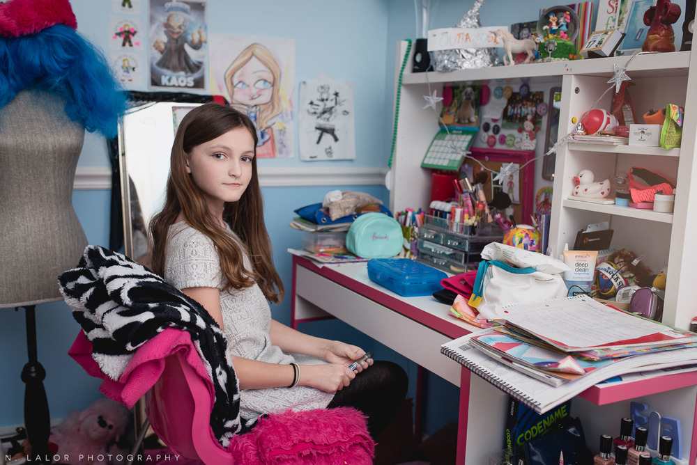 Tween girl sitting at her desk in her well-decorated room. Editorial-style photo by N. Lalor Photography.
