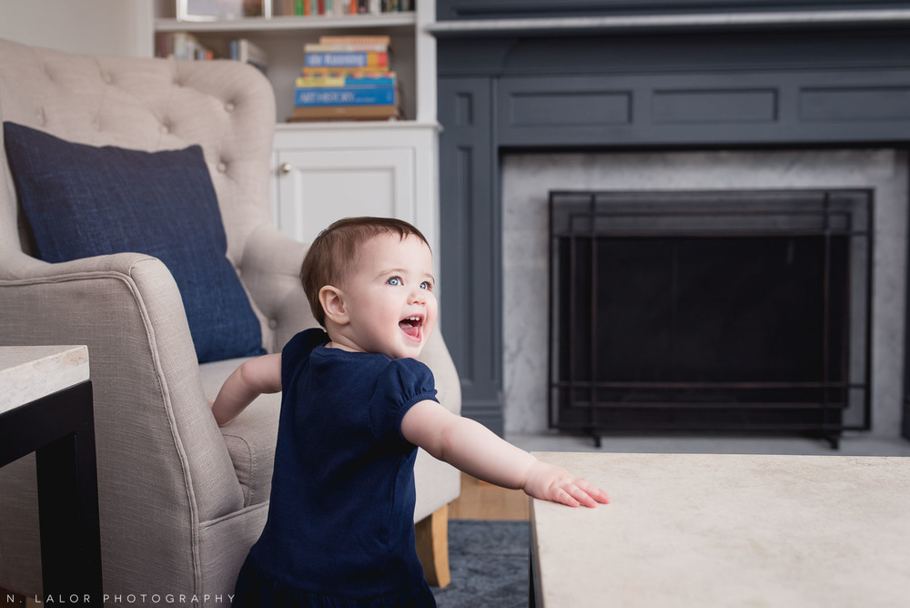 1-year old baby girl in the living room. Casual lifestyle portrait by N. Lalor Photography.
