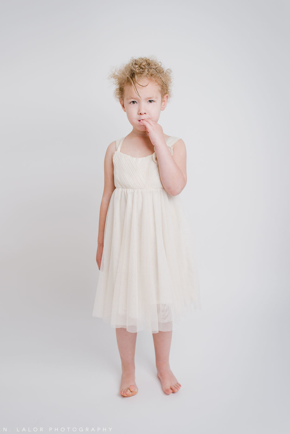 Simple studio portrait of a 4-year old girl wearing a white dress. By N. Lalor Photography. Greenwich, CT.