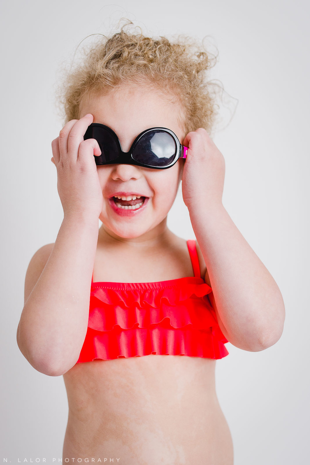 Simple and fun studio portrait of a 4-year old girl wearing a red swim suit and sunglasses. By N. Lalor Photography. Greenwich, CT.