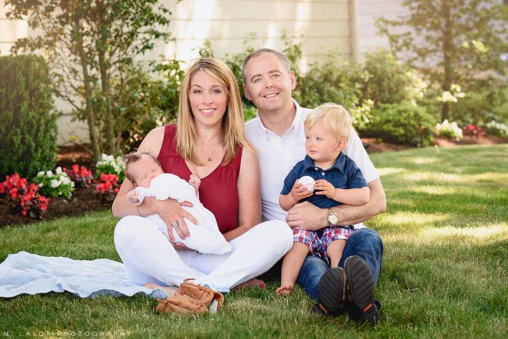 Outdoor family photo with their toddler and newborn. Lifestyle family session by N. Lalor Photography. Fairfield County, Connecticut.