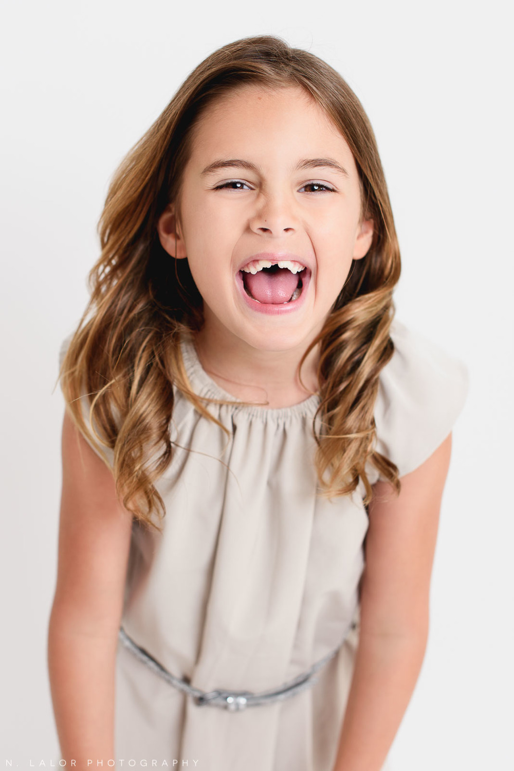 Laughs. Editorial studio portrait of 6-year old girl by N. Lalor Photography in Greenwich, Connecticut.