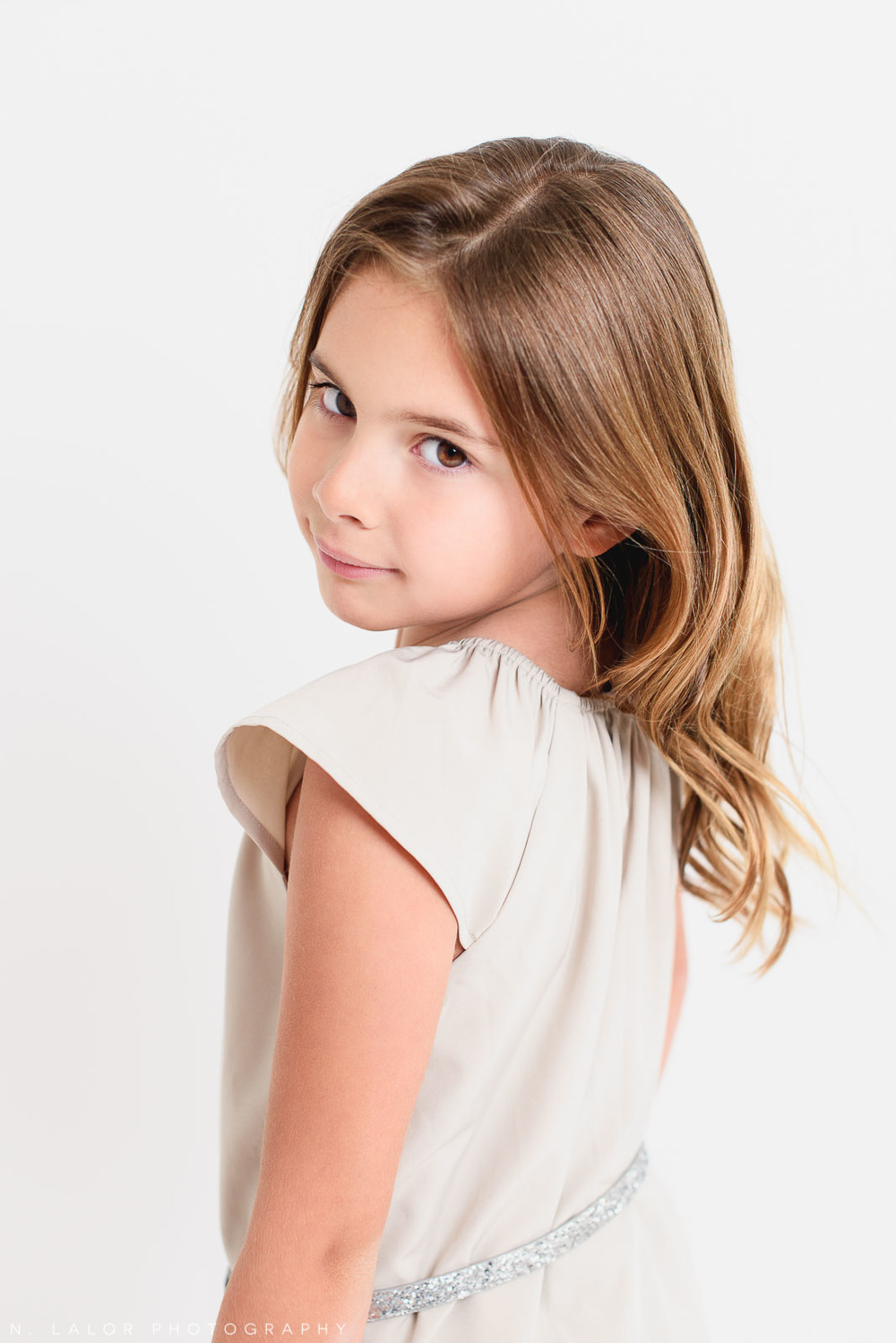 Over the shoulder. Editorial studio portrait of 6-year old girl by N. Lalor Photography in Greenwich, Connecticut.