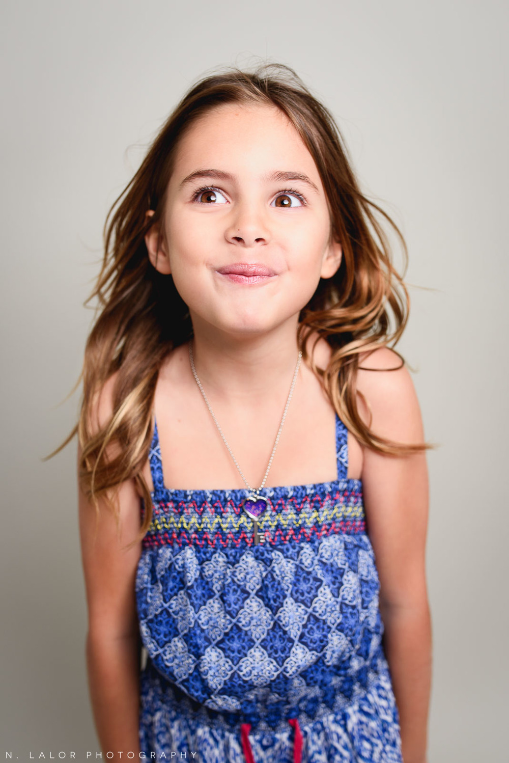 That mischievous smile! Editorial studio portrait of 6-year old girl by N. Lalor Photography in Greenwich, Connecticut.