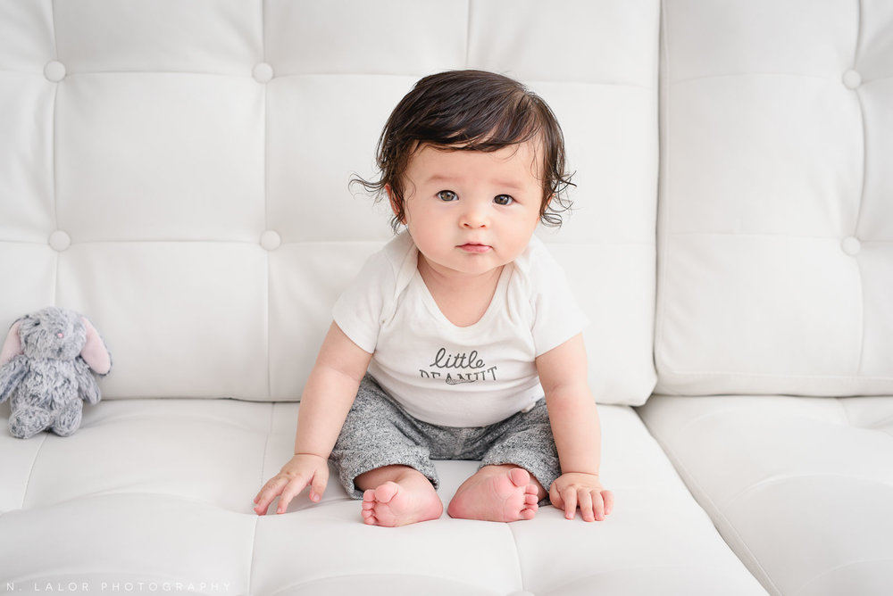 Sitting on the couch. 6-month old baby studio photoshoot with N. Lalor Photography in Greenwich, Connecticut.