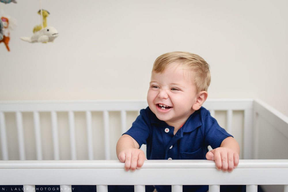 11-month old boy laughing in his crib. At home family photo session in Riverside, Connecticut with N. Lalor Photography.