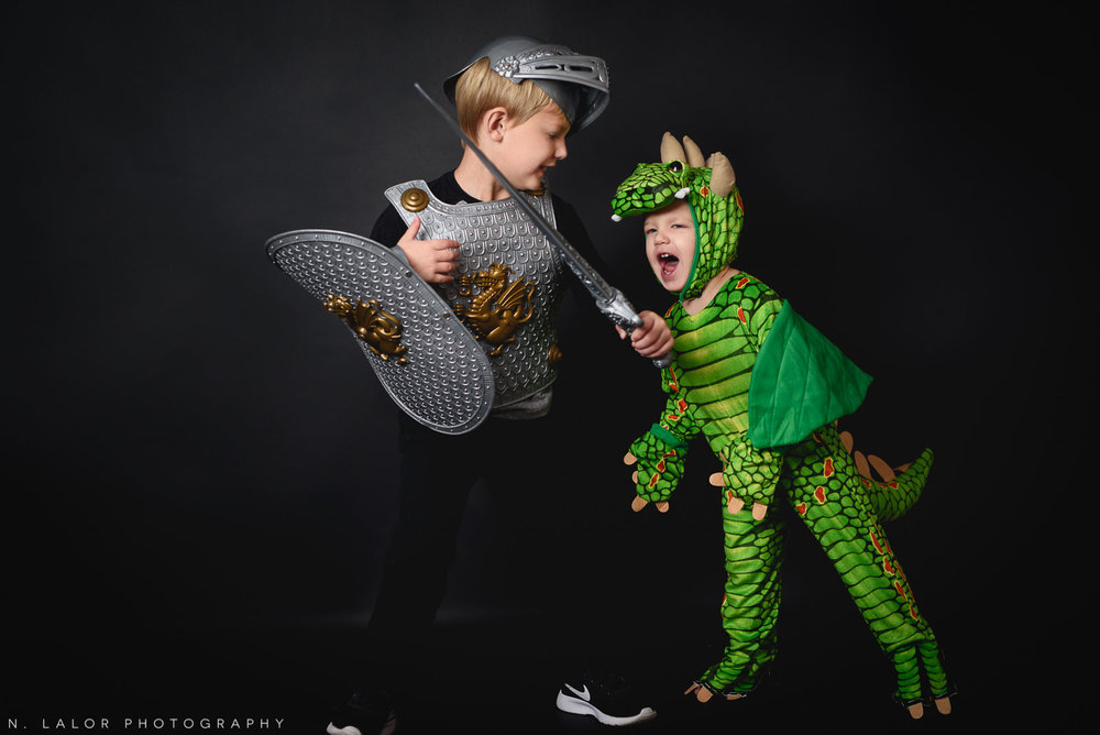 A knight battling a dragon. Kids Halloween Portrait by N. Lalor Photography in Greenwich, Connecticut.