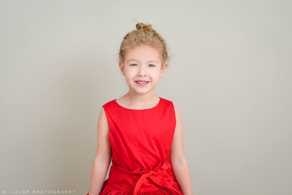 The little sister, dressed in red. Greenwich CT Kids Photo Studio Portraits by N. Lalor Photography