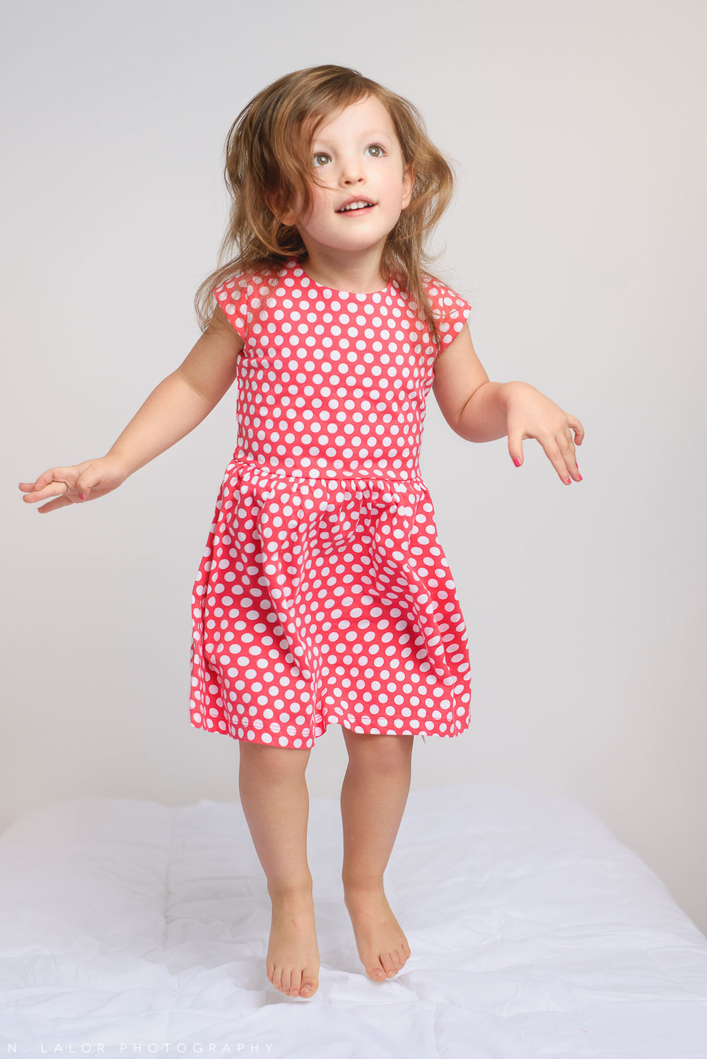 Jumping on the bed, 2 year old girl. Simple studio portrait by N. Lalor Photography in Greenwich, Connecticut.