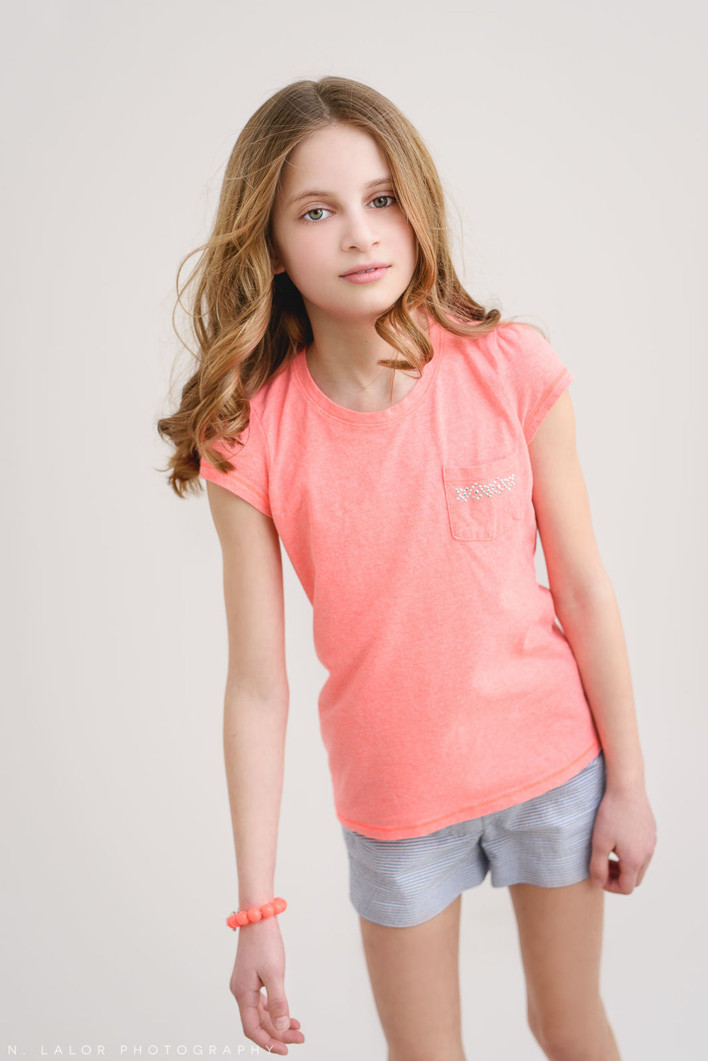 Pink shirt and bracelet. Tween Studio photoshoot by N. Lalor Photography, located in Greenwich, CT.