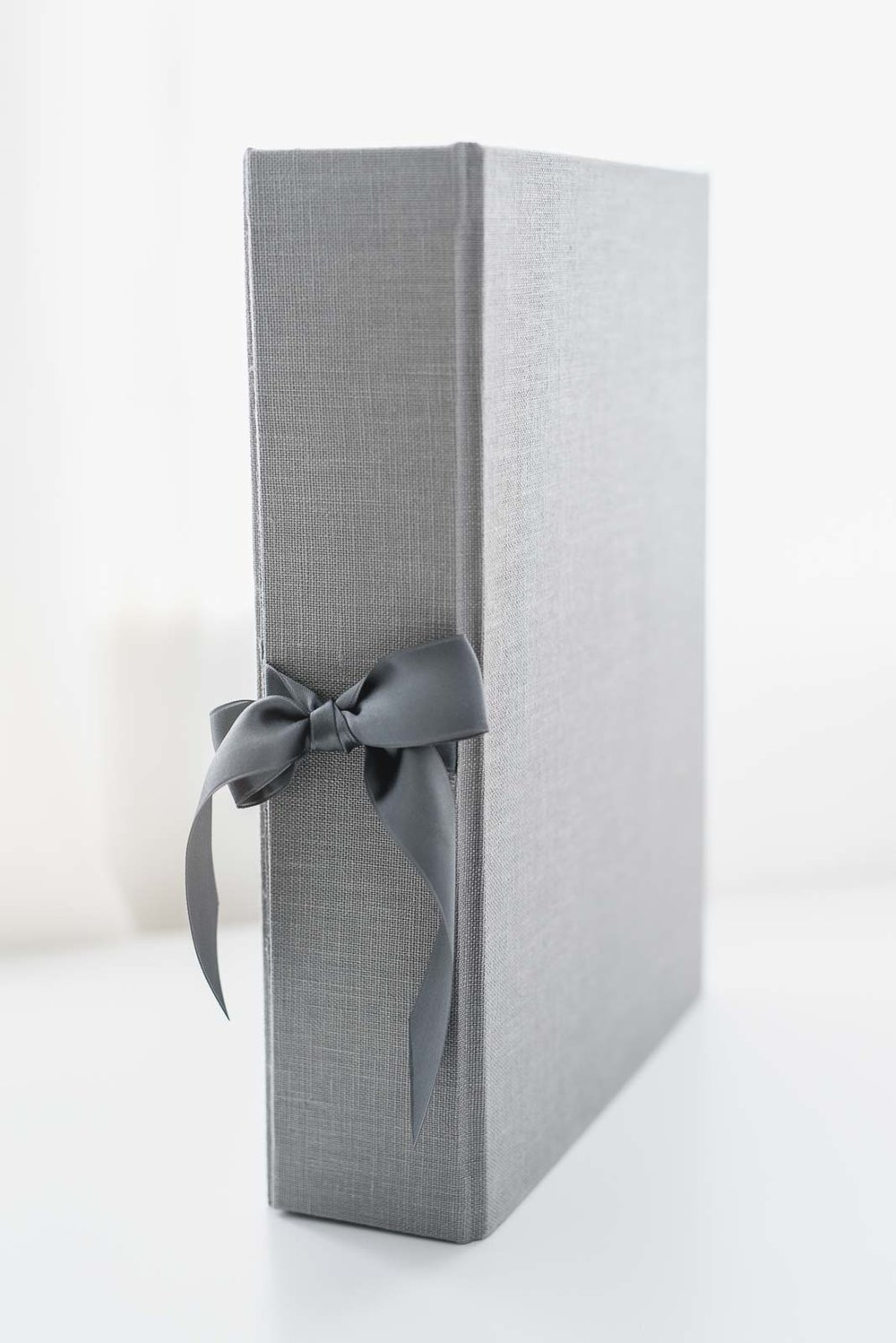 N. Lalor Photography print products - Cypress Albums folio box in sea mist gray linen and gray bow accent.