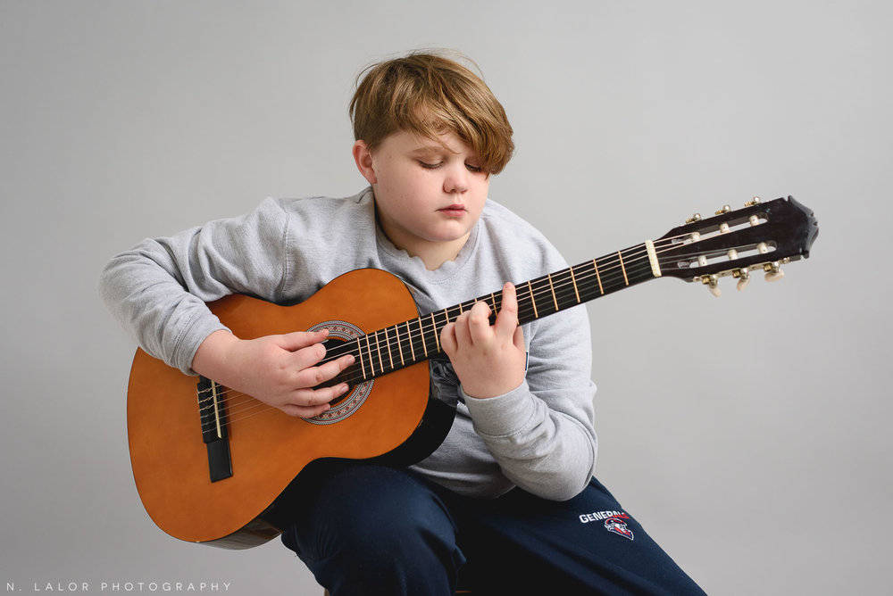 Benjy playing guitar. Teen family photo session with N. Lalor Photography. Greenwich, Connecticut studio photographer.