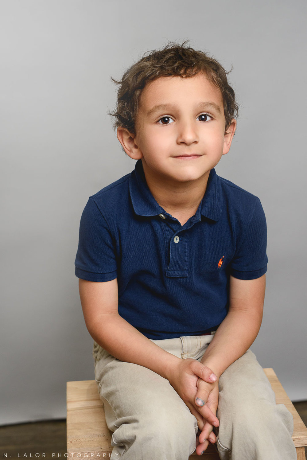 Active little boy. Simple studio portrait by N. Lalor Photography. Taken in New Canaan, CT.