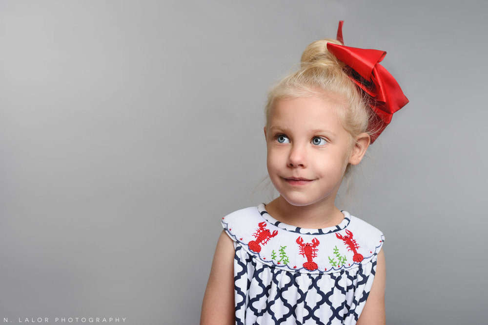 Red bow and dress. Simple studio portrait by N. Lalor Photography. Taken in New Canaan, CT.