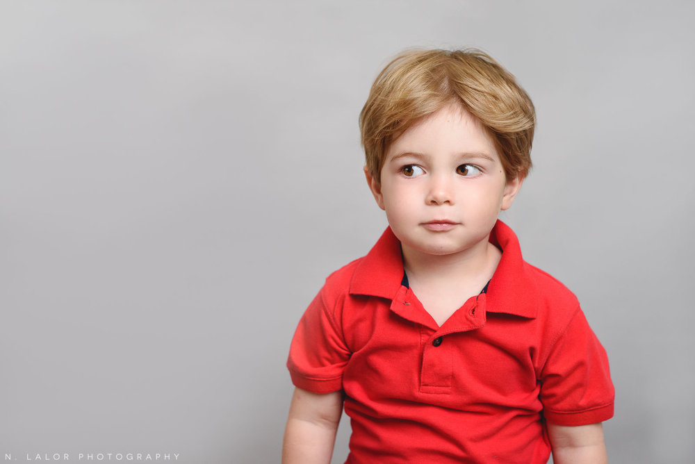 Adorable little boy with a red polo shirt. Simple studio portrait by N. Lalor Photography. Taken in New Canaan, CT.