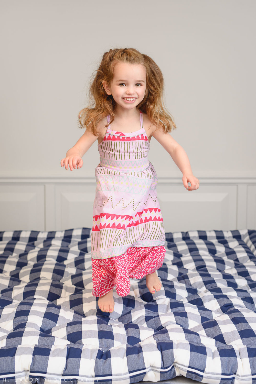 Little girl jumping on a luxury mattress. Limited-edition exclusive event with N. Lalor Photography and Hästens in Greenwich, Connecticut.